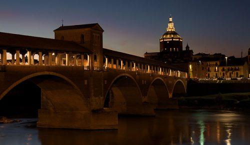 l Ponte Coperto di Pavia sul Ticino di sera, con sullo sfondo il Duomo di Pavia